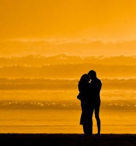 Lovers embracing on the beach at sundown on Morro Strand State B